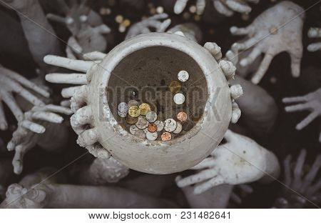 Strange Hands Hold A Pot Of Coins. Chiang Rai, White Temple. Thailand.