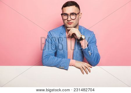 Portrait Of Handsome Thoughtful Businessman In Blue Jacket And Eyeglasses Isolated On Pink Backgroun