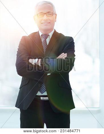 Full length portrait of senior businessman standing against whit