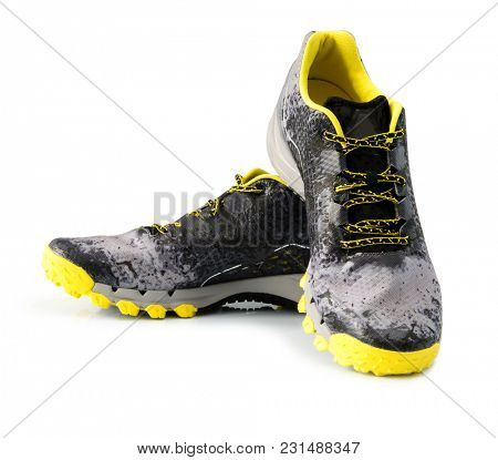 Pair of black and yellow male sport sneakers on white wooden background