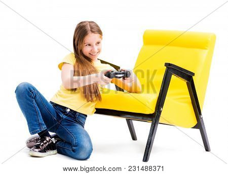 Lovely teen girl in yellow tshirt playing with joystick ona white background