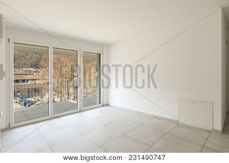 Empty living room with large windows and terrace. View on a valley.