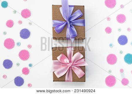 Two Gift Boxes On Festive Background Of Pastel Confetti. Flat Top View