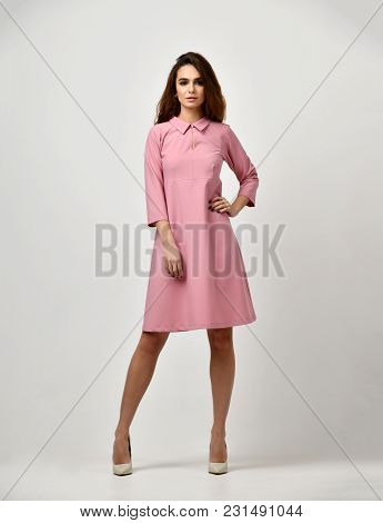 Woman In Pink Pastel Color Winter Dress Standing On Gray Background