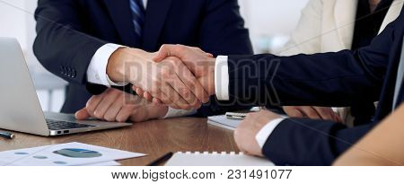 Close Up Of Business People Shaking Hands At Meeting Or Negotiation In The Office. Partners Are Sati
