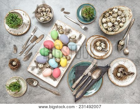 Easter Decoration Colorful Eggs And Green Plants. Holidays Table Setting Background