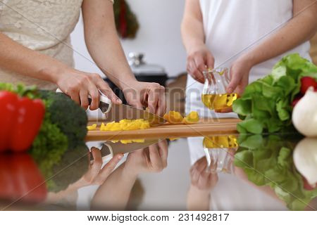 Closeup Of Human Hands Cooking In Kitchen. Mother And Daughter Or Two Female Cutting Bell Pepper For