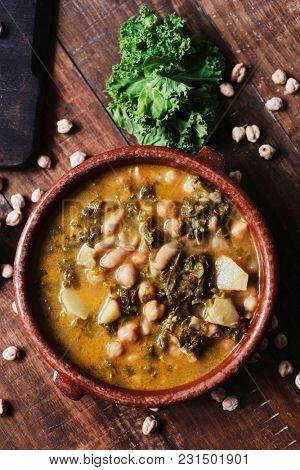 high angle view of an earthenware bowl with kale stew with potatoes and chickpeas, on a rustic wooden table sprinkled with some dry chickpeas