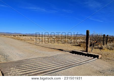 Cattle Guard, Gate, And Fence  Of Ranch Land In A Desert Environment