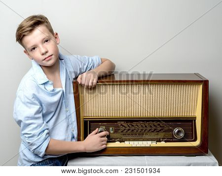 Boy Teenager Near Old Radio. The Concept Of Retro And Nostalgia, A Happy Childhood.