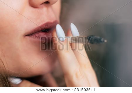 A Woman Smokes Weed Cannabis A Joint And A Lighter In His Hands. Smoke On A Black Background. Concep