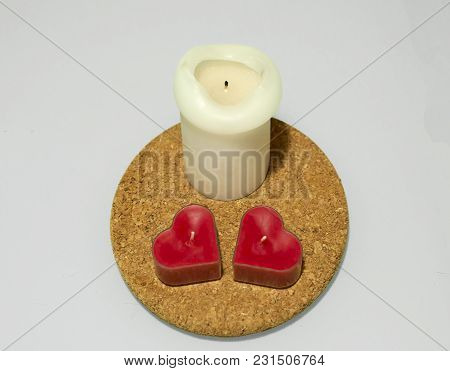 One Tall White And Two Heart Shaped Red Candles On Round Cork Hot Pad On White Background