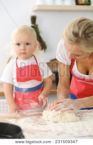 Mother And Her Cute Daughter Hands Prepares The Dough On Wooden Table. Homemade Pastry For Bread Or