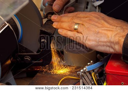 Hand Of A Married Man Grinding Down A Drill Bit On A Grinder In His At Home Workshop.  Sparks Are Fl