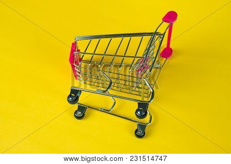 Shopping Cart Or Supermarket Trolley On Yellow Background, Business Finance Shopping Concept.