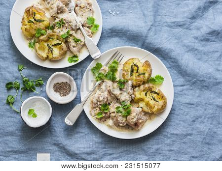 Smashed Roasted Sage Butter Potatoes And Mustard Cream Sauce Meat - Tasty Lunch On Blue Background,