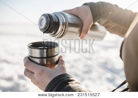 Pouring The Tea From The Thermos Outdoors. Cold Snow And Spring Light