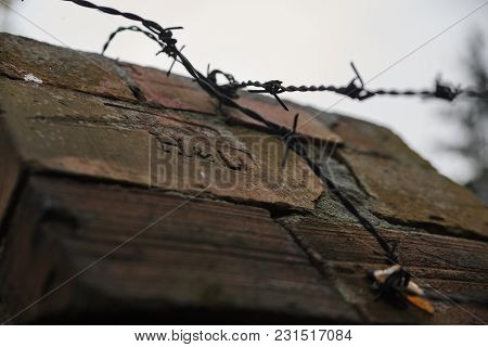 Red Bricks With A Stamp And Barbed Wire.