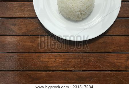 Cropped In A Half Shot Of Plain Thai Rice On White Plate Put On Brown Wooden Table With Copy Space A
