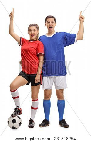 Full length portrait of a young cheerful couple with a football dressed in sportswear holding their index fingers up isolated on white background