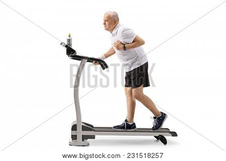 Full length profile shot of a mature man walking on a treadmill and having a heart attack isolated on white background
