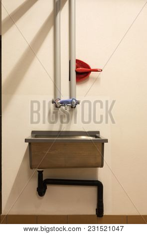 Detail of dustpan and broom with hydraulic pipes and sink. Closeup