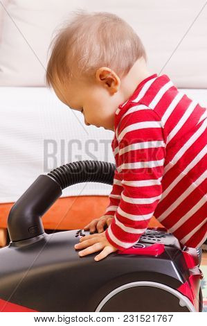 Little Baby Boy Playing With Vacuum Cleaner At Home