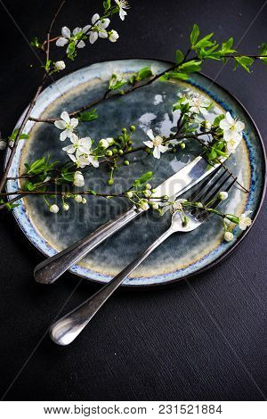 Spring Floral Concept With Blooming Cherry Tree Branches And Serving With Rustic Tablewares On Dark