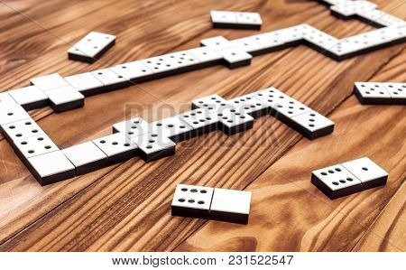 Domino Game On The Brown Wooden Table.