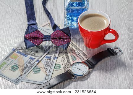 Man Perfume, Bow Tie, Cup Of Coffee, Watch With A Black Leather Strap And Dollar Bills On Grey Woode