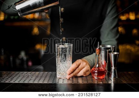 Barman Puring A Fresh Alcoholic Drink From Shaker Into A Cocktail Glass On The Bar Counter Against D