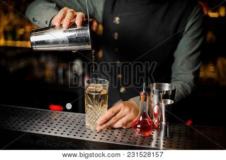 Barman Puring A Sweer Alcoholic Drink From Shaker Into A Cocktail Glass On The Bar Counter Against D