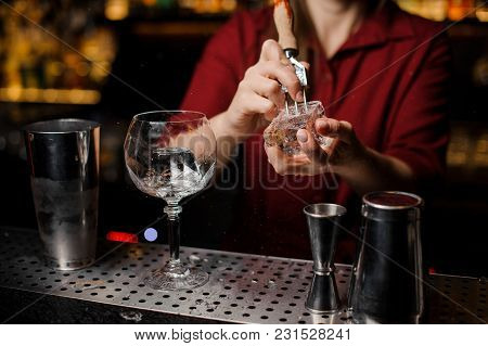 Female Barman Preparing Ice Cube For Making A Fresh Alcoholic Cocktail On The Bar Counter