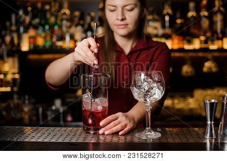 Beautiful Female Barman Stirring Fresh And Sweet Red Alcoholic Drink With Ice Cubes In A Glass