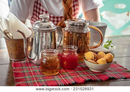 Tea Drinking. Tea Pot, Homemade Honey, Jam, Muffins And Cup On Red Fabric