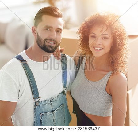 Happy married couple on the background of a new apartment