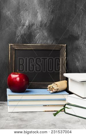 School Attributes - Black Board, Books, Colored Pencils, Notebook, Apple On Dark Background. Copy Sp