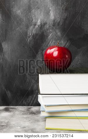 Pile Of Various Books And Red Apple On Dark Background. Copy Space