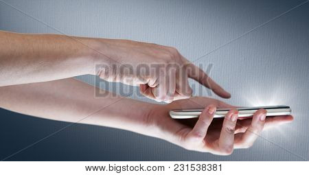 Digital composite of Hands with phone and flare against navy background