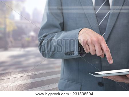 Digital composite of Man mid section with tablet against blurry street with flares