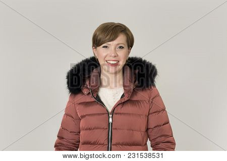 young attractive and happy red hair Caucasian woman on her 20s or 30s posing cheerful and smiling wearing warm winter jacket with fur hood isolated on grey background in seasonal fashion concept poster
