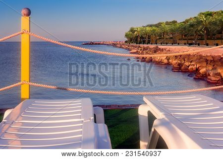 Chaise Lounges On A Grass Near The Coastline Of The Sea With The Blue Sky