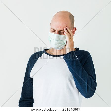 Sick man wearing surgical mask having a headache