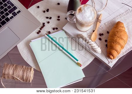 The Laptop And Notebook With Pencils On A Table And Coffee With Croissant On A Tray