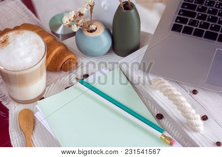 The Laptop And Notebook With Pencils On A Table And Coffee With Croissant On A Doily