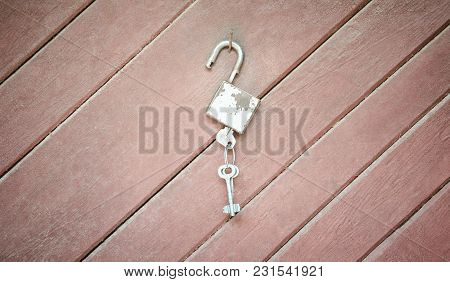 Gray Open Lock With Keys On Wooden Background Concept