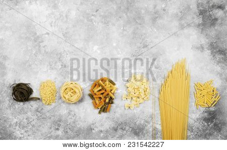Various Raw Pasta On Gray Background. Top View; Copy Space. Food Background