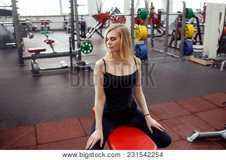 Young Slender Woman In Gym Posing Against A Lot Of Fitness Equipment On Background. She Wears Black