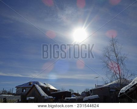 Winter Sky In Small Village. Lot Of Snow, House Roofs And Naked Trees. Sunny Day, Sun With Flares. R