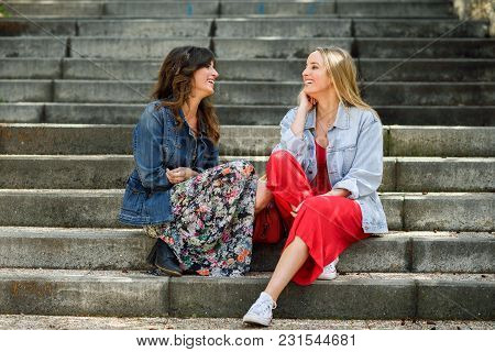 Two Young Women Talking And Laughing On Urban Steps. Two Girls Wearing Casual Clothes. Lifestyle Con